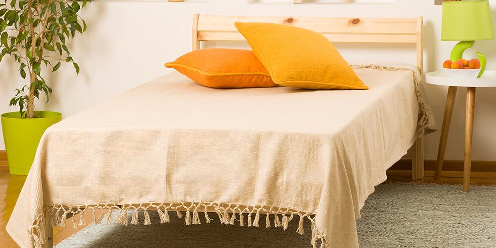 Spavaća soba sa bež prostirkom za krevet sa jastucima na njoj