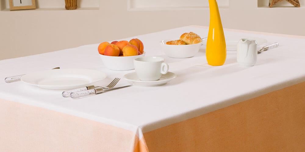 postavljen ugostiteljski sto na belo-narandzastom stolnjaku